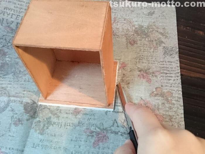 ペーパーを木箱に当てて切り出す